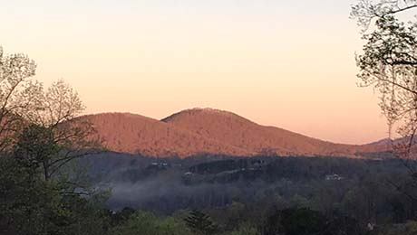 A peach sky behind gentle, wooded hills