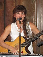 Cathy Murch playing a guitar and singing