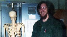 Ostell standing next to a replica of the human skeleton