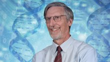 Ostell headshot in front of a backdrop comprised of DNA molecules