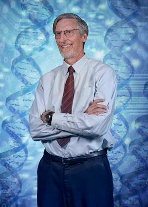 Ostell stands with arms folded in front of a backdrop comprised of DNA molecules
