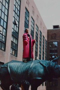 Ostell in crimson academic regalia stands on the back of a bronze rhino