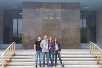 A family of four in front of NLM's main entrance