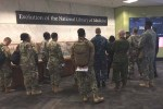 A dozen uniformed men and women listen to the NLM tour guide