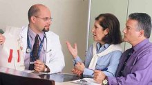 A doctor consults with his patient and her spouse