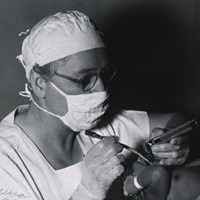 Apgar, in surgical mask and cap, tends to a infant