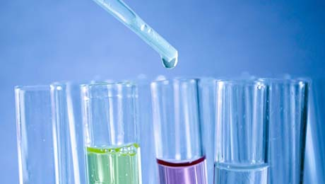 test tubes, some filled with colored liquids, against a blue background