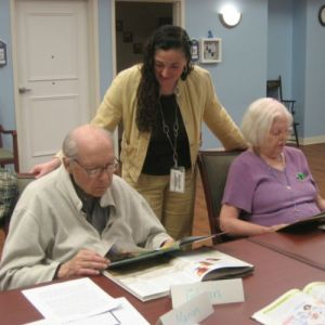 A woman stands about two older adults who are reading