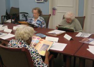 Three older adult women reading