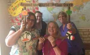 Four women pose in front of a map of the world