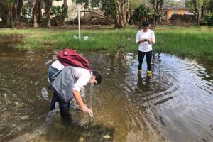 two students take readings in knee-deep water