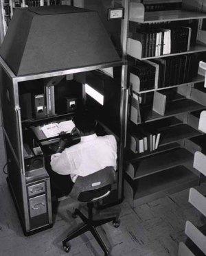 man holds a book under an overhead camera