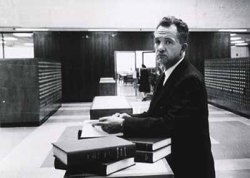 candid view of Dr. Rogers consulting the card catalog