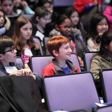 one middle schooler in the audience smiles broadly, looking excited to be there, while others look on