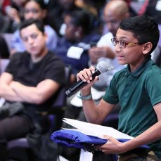 a middle school boy asks a question into a microphone