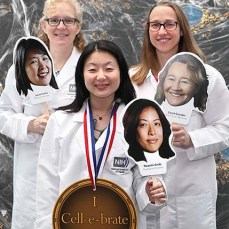 "three young women holding cardboard cutouts of women scientists pose with a sign saying ""I Cell-e-brate Science."""