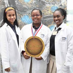 "three young women pose with a sign saying ""I Cell-e-brate Science."""