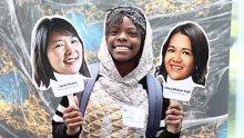 A African-American teenaged girl holds up cardboard cutouts of two women scientists