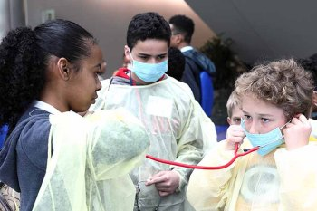 A middle schooler uses a stethoscope to listen to a young woman's heartbeat