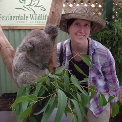 A young woman wearing a summer hat stands next to a sleeping koala