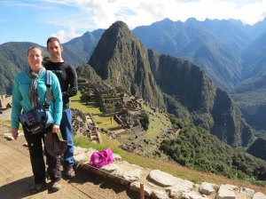 a young couple pose with the Incan citadel, Machu Picchu, looming behind them