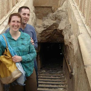 a young couple pose at the top of stairs descending into a stone structure