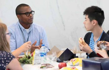 A young African-American man engages with teens over lunch