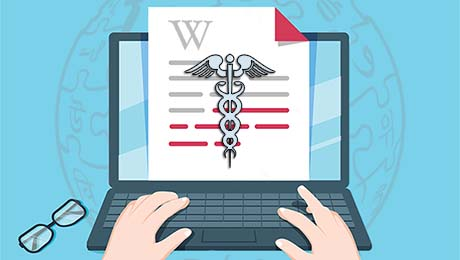 """a person types on a laptop on which is visible a page showing the Wikipedia """"W"""" and the medical caduceus symbol"""