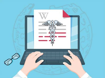 "a person types on a laptop on which is visible a page showing the Wikipedia ""W"" and the medical caduceus symbol"