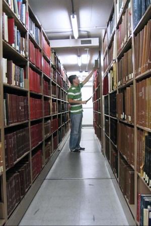 a man pulls a book off a library shelf