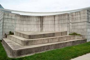 three tiers of concrete each smaller than the one below rest in front of a curved wall of concrete block