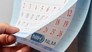 Hand is flipping through the wall calendar on which is visible the NLM logo