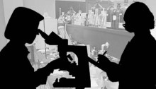 silhouettes of two women scientists against a black & white photo of a lab bench
