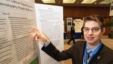 A young man points toward his academic poster