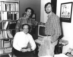Black & white photo of Dennis Benson (seated), David Lipman and Jim Ostell (both standing), circa 1988