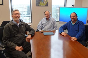 three men sit at a conference table and smile