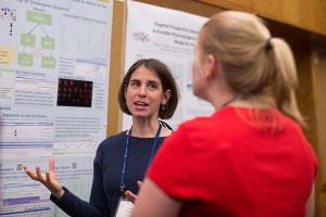 Schneider talks to a colleague in front of her research poster