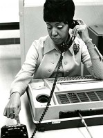 A woman holds a telephone receiver to her ear while pressing keys on the phone
