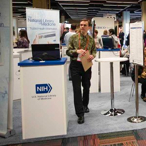 A man walks through the NLM exhibit booth